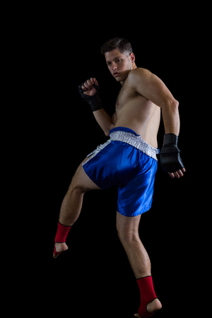 grappling: Boxer performing boxing stance against black background Stock Photo