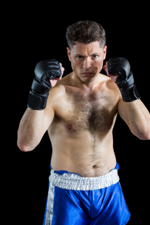grappling: Portrait of boxer performing boxing stance against black background