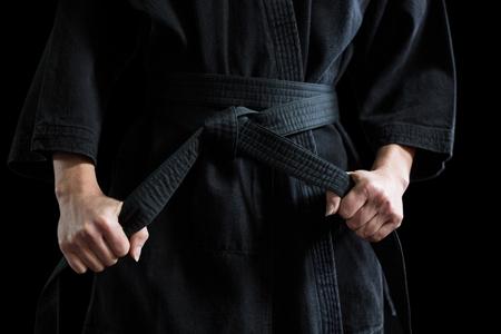 Confident karate player holding his belt against black background