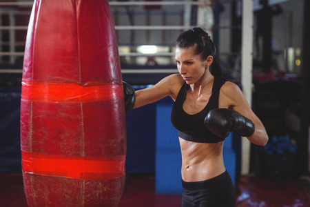 grappling: Female boxer practicing boxing with punching bag in fitness studio Stock Photo