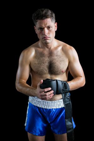 grappling: Portrait of boxer wearing grappling gloves against black background