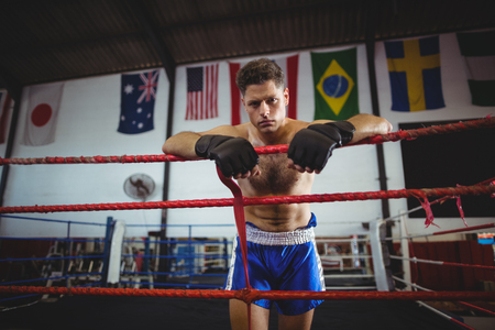 grappling: Portrait of tired boxer leaning on boxing ring
