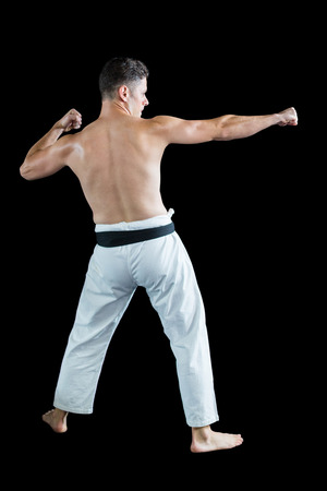 Rear view of karate fighter performing karate stance against black background Stock Photo