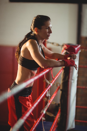 female boxer: Thoughtful female boxer standing in boxing ring