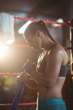 female boxer: Female boxer wearing blue strap on wrist in boxing ring