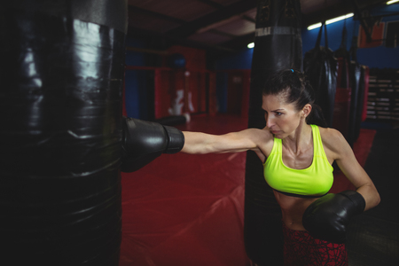 female boxer: Female boxer practicing boxing with punching bag in fitness studio Stock Photo