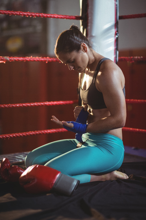 wrist strap: Female boxer wearing blue strap on wrist in boxing ring