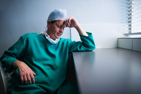 tensed: Tensed male surgeon sitting at window in hospital