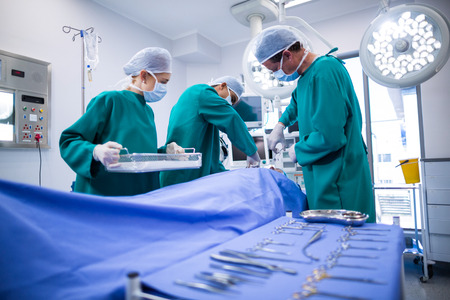 surgical tray: Surgeons performing operation in operation theater of hospital