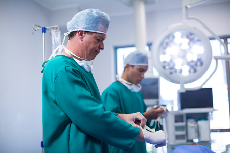 Surgeon wearing surgical gloves in operation theater of hospital Stock Photo