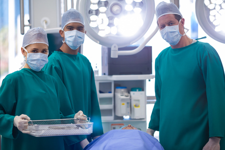surgical tray: Portrait of surgeons performing operation in operation theater of hospital Stock Photo