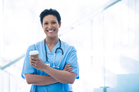 disposable cup: Female nurse standing with disposable cup in corridor of hospital Stock Photo