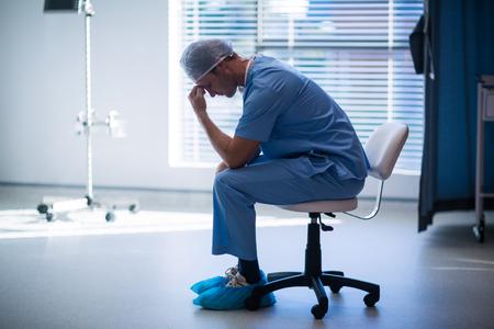 Tensed male nurse sitting in corridor of hospital