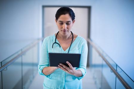 Female doctor using digital tablet in corridor of hospital