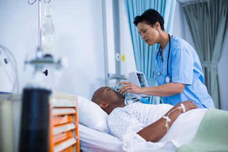 Nurse adjusting oxygen mask on patient mouth in ward