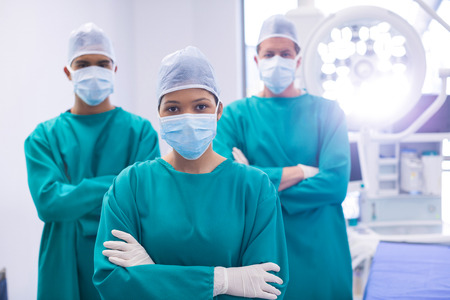 Team of surgeons wearing surgical mask in operation theater of hospital Stock Photo
