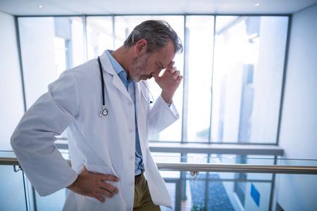 病院の廊下に立っている悲しい医師