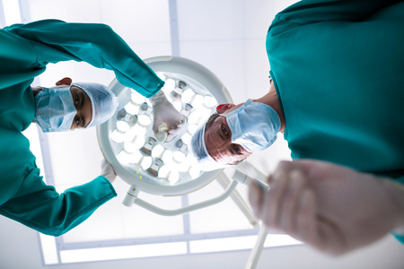Surgeons operating in operation theater in hospital Stock Photo