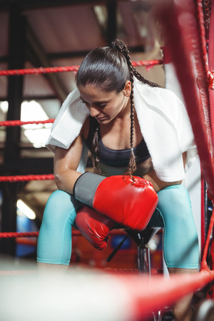 Tired female boxer sitting in the ring in fitness studio