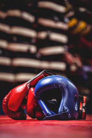 Pair of boxing gloves and headgear in boxing ring