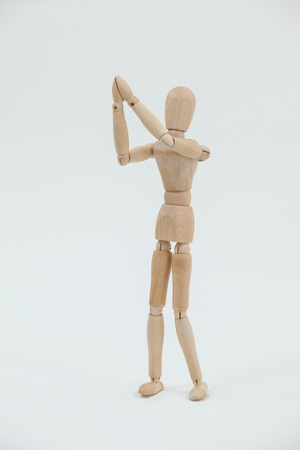 joined: Wooden figurine standing with both the hands joined against white background
