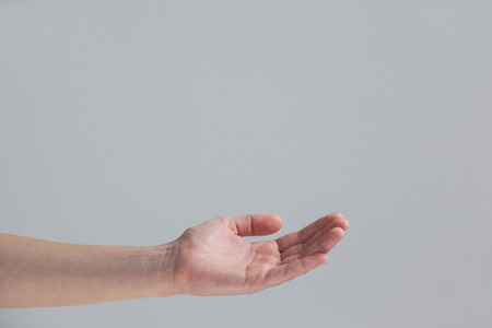 cupped: Close-up of cupped hand of a woman against grey background