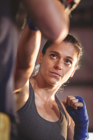 female boxer: Female boxer practicing in the ring at fitness studio Stock Photo