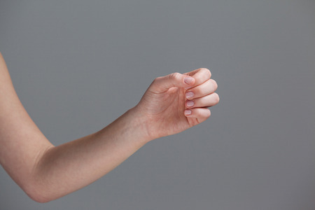 grey nails: Hand of a woman with manicured nails against grey background