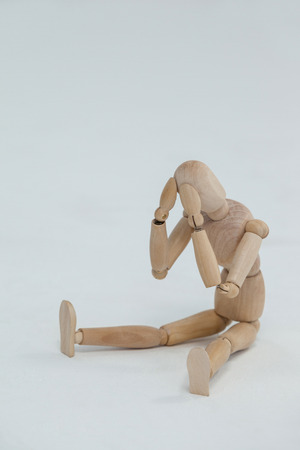 tensed: Tensed wooden figurine sitting with hands on head against white background