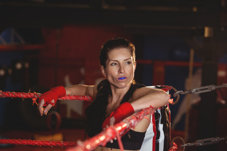 female boxer: Thoughtful female boxer sitting in the ring at fitness studio Stock Photo