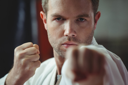 Karate player performing karate stance in fitness studio Stock Photo