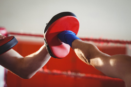 Female boxer practicing in the ring at fitness studio Stock Photo