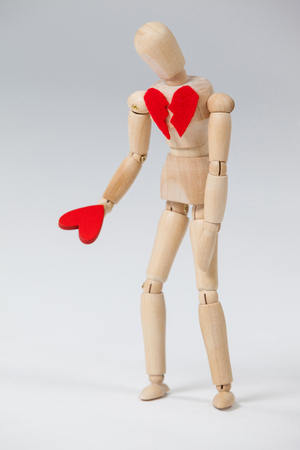 Wooden figurine with a broken heart and holding a red heart against white background Stock Photo