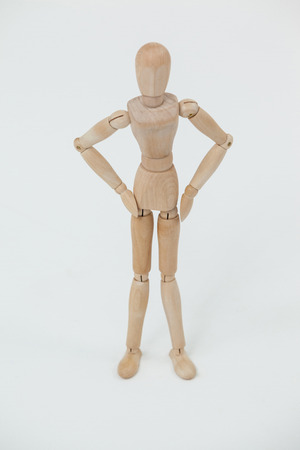 waiting posture: Wooden figurine standing with hands on hips against white background