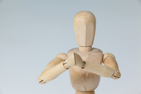 Wooden figurine with both hands joined against white background