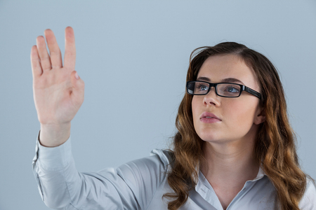 wearing spectacles: Beautiful woman wearing spectacles pretending to touch an invisible screen on grey background