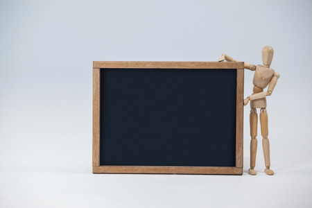 Wooden figurine standing beside a slate board against white background Stock Photo