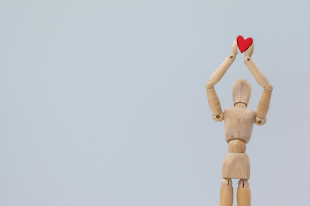 Wooden figurine standing and holding a red heart on top against white background