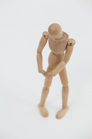 Wooden figurine standing with hands on knee against white background Stock Photo
