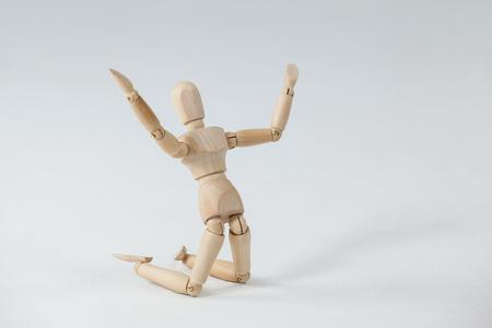 arrodillarse: Estatuilla de madera de rodillas con los brazos abiertos contra el fondo blanco