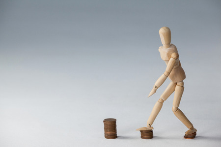 stepping: Wooden figurine stepping on stack of coins against white background