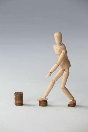 Wooden figurine stepping on stack of coins against white background