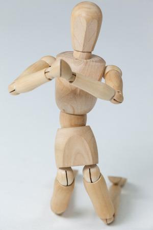 arrodillarse: Estatuilla de madera de rodillas con ambas manos juntas contra el fondo blanco