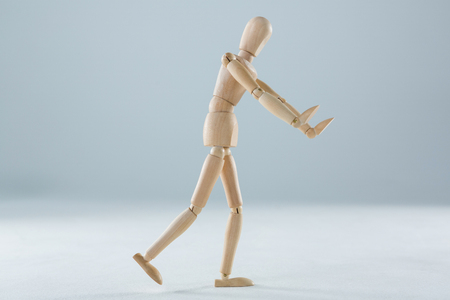 invisible object: Wooden figurine pretending to push an invisible object against white background Stock Photo