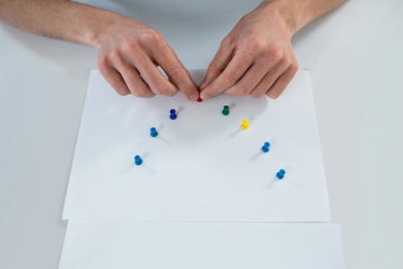 push pin: Hand of man attaching push pin on paper