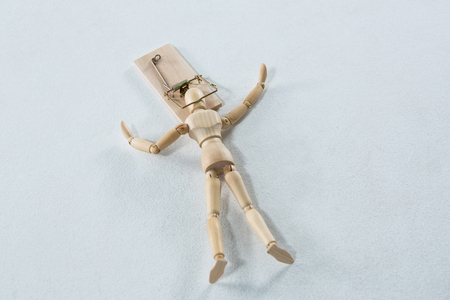 entrapment: Wooden figurine caught in the mouse trap against white background