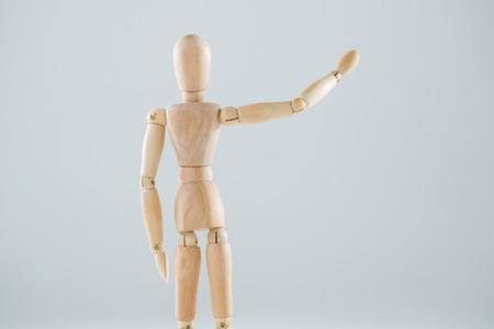 waiting posture: Wooden figurine hailing against white background