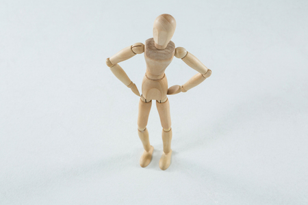 waiting posture: Wooden figurine standing with hands on his waist against white background