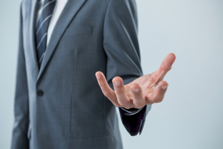 Mid section of businessman making hand gesture Stock Photo