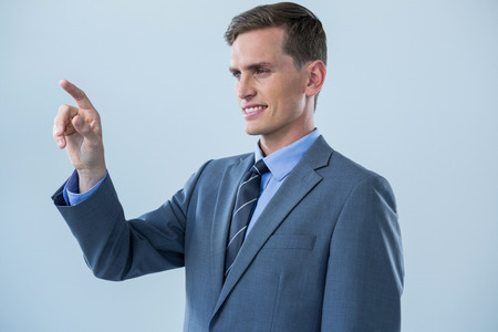 invisible: Smiling businessman touching an invisible screen against white background